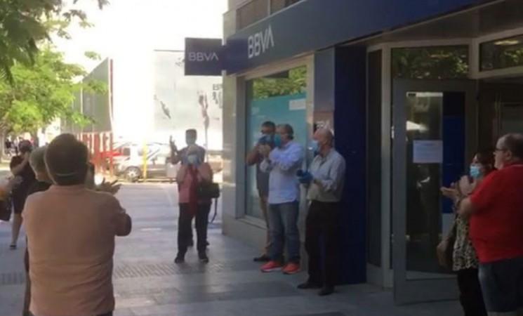 Los empleados de una sucursal del BBVA son aplaudidos por un grupo de clientes